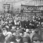"""A demonstration of workers from the Putilov plant in Petrograd (modern day St. Peterburg), Russia, during the February Revolution. The left banner reads (misspelt) """"Feed [plural imperative] the children of the defenders of the motherland""""; the right banner, """"Increase payments to the soldiers' families - defenders of freedom and world peace"""". Both refer to the economic toll the First World War was having on civilian life, February 1917 (probably around March 7 [O.S. February 22]) Photo: Unknown. Public Domain."""
