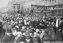 "A demonstration of workers from the Putilov plant in Petrograd (modern day St. Peterburg), Russia, during the February Revolution. The left banner reads (misspelt) ""Feed [plural imperative] the children of the defenders of the motherland""; the right banner, ""Increase payments to the soldiers' families - defenders of freedom and world peace"". Both refer to the economic toll the First World War was having on civilian life, February 1917 (probably around March 7 [O.S. February 22]) Photo: Unknown. Public Domain."