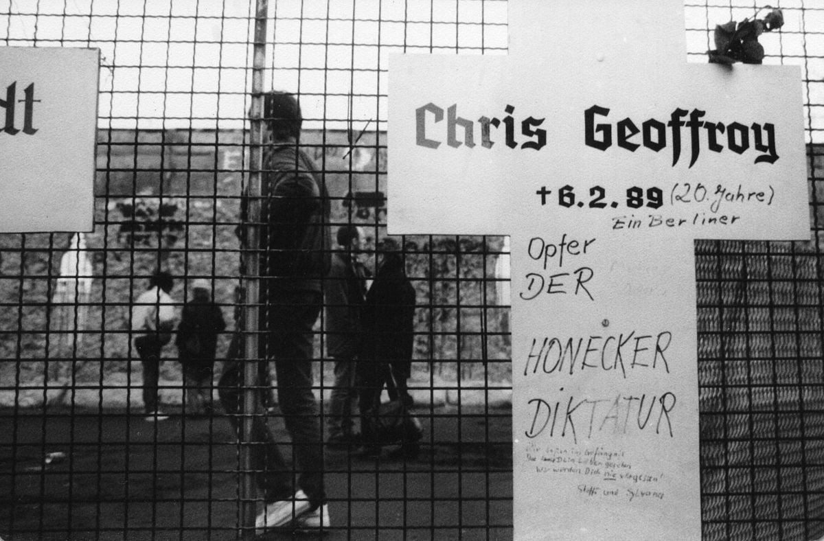 """Commemorative tablet to Chris Gueffroy, the last person to die trying to escape across the Berlin Wall. In the background is the partly destroyed Wall, near Reichstag (building). Winter 1989 /90. Author: Stefan Richter. (CC BY-SA 3.0). Source: <a href=""""https://commons.wikimedia.org/wiki/File:Chris_Gueffroy.jpg"""">Wikimedia Commons.</a>"""