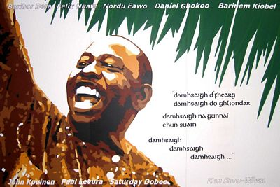 """Mural depicting Ken Saro-Wiwa in County Mayo, Ireland; some of his poetry is displayed (translated into Irish), as well as the names of the other eight activists of the """"Ogoni Nine"""" that were executed. (Kilde: Wikipedia.org)"""