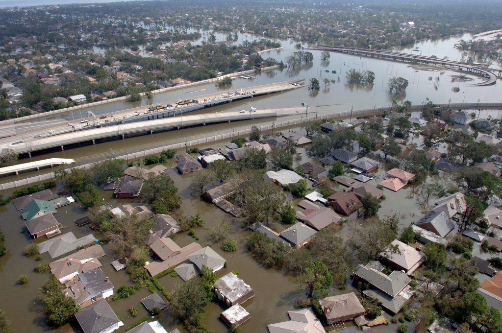 """New Orleans, La., August 29, 2005 -- Aerial of a flooded New Orleans neighborhood with a roadway going down into flood waters. New Orleans is being evacuated as a result of floods from hurricane Katrina. Thousand of people have been rescued from the flood waters by moving to their roofs and attics. Photo by Jocelyn Augustino/FEMA Date: 30 ugust 2005. Public domain. Source: <a href=""""https://commons.wikimedia.org/wiki/File:FEMA_-_15012_-_Photograph_by_Jocelyn_Augustino_taken_on_08-30-2005_in_Louisiana.jpg"""">Wikimedia Commons</a>"""