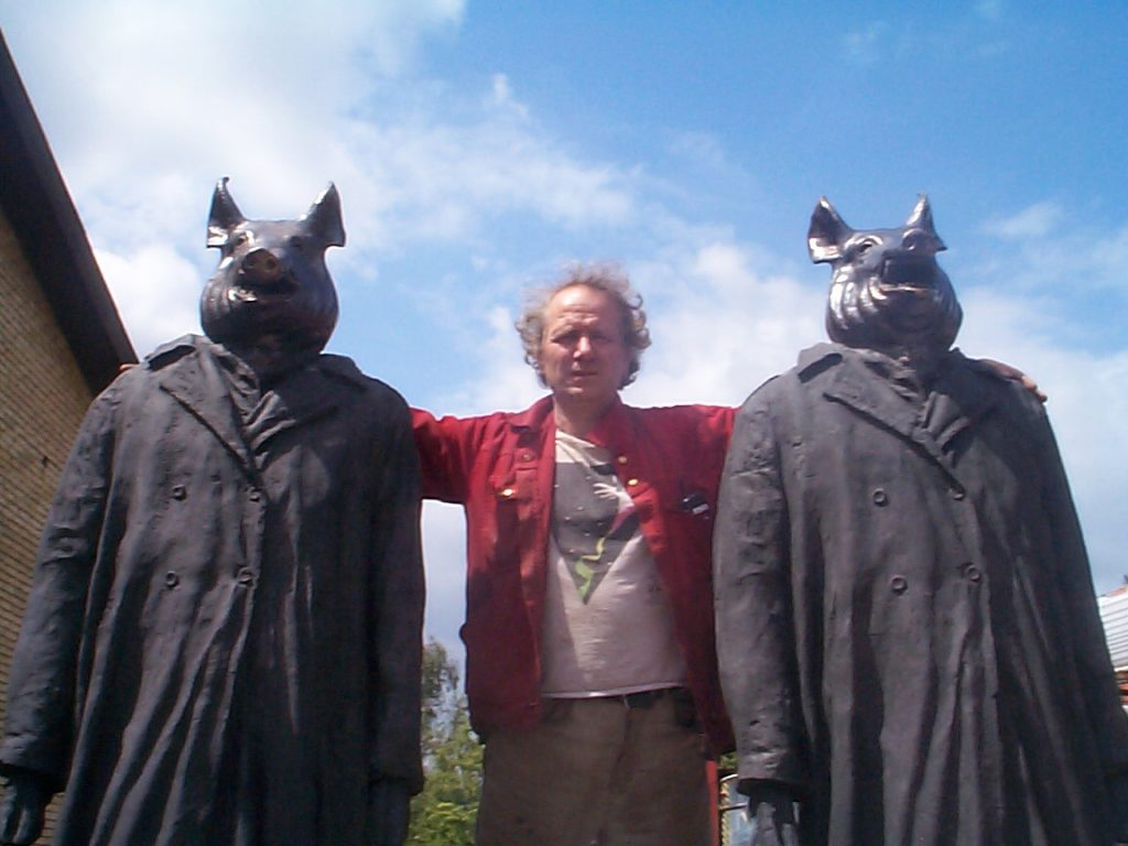 """Jens Galschiøt with """"My Inner Beast"""" sculptures, 16 May 2001. Author: Jens Galschiøt. (CC BY-SA 3.0). Source: <a href=""""https://commons.wikimedia.org/wiki/File:My_Inner_Beast_and_Jens_Galschi%C3%B8t.jpg"""">Wikimedia Commons.</a>"""