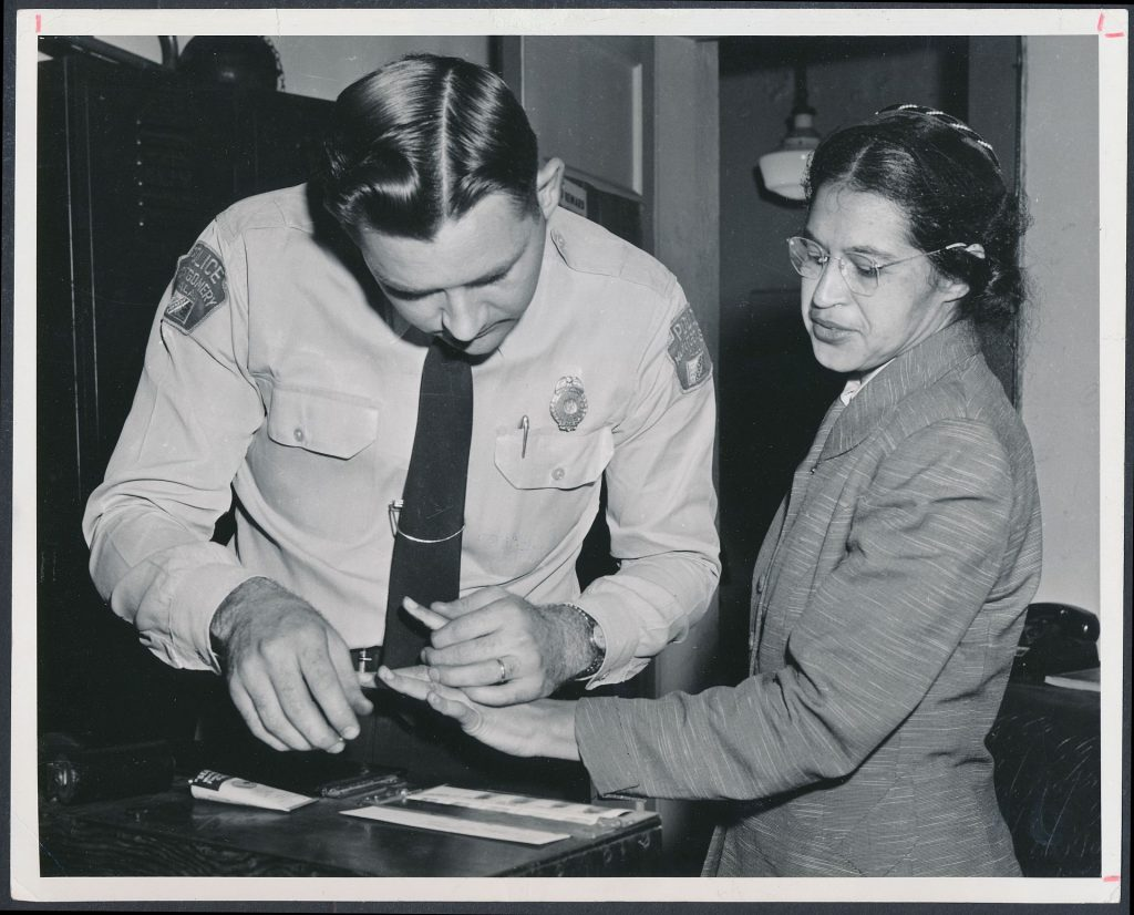 """Rosa Parks being fingerprinted by Deputy Sheriff D.H. Lackey after being arrested for boycotting public transportation, Montgomery, Alabama, February, 1956. Author: The Plain Dealer, a newspaper in Chicago. public domain Source: <a href=""""https://commons.wikimedia.org/wiki/File:Rosa_Parks_being_fingerprinted_by_Deputy_Sheriff_D.H._Lackey_after_being_arrested_for_refusing_to_give_up_her_seat_for_a_white_passenger_on_a_segregated_municipal_bus_in_Montgomery,_Alabama_-_Original.jpg"""">Wikimedia Commons</a>"""