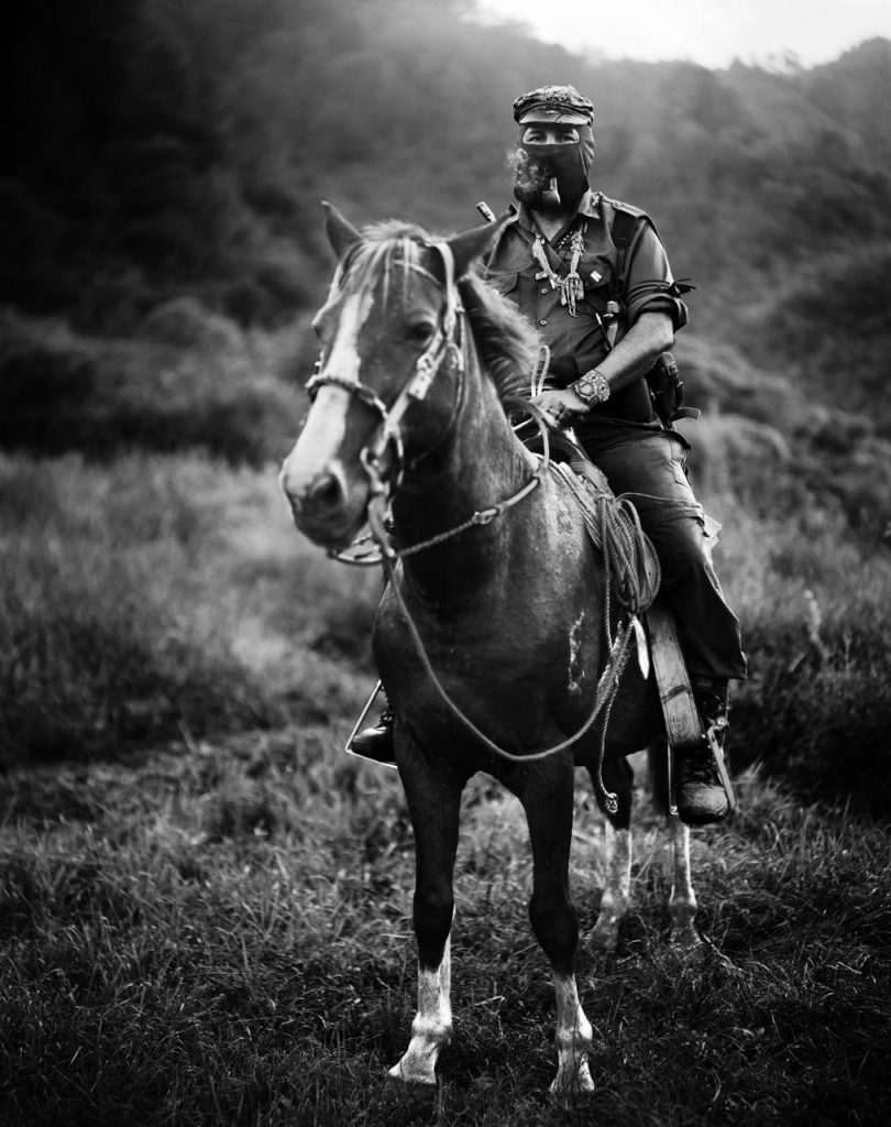 Subcomandante Marcos, the spokesman of the Ejército Zapatista de Liberación Nacional, striking a pose, smoking a pipe atop a horse in Chiapas, Mexico. 1996.Photo: (Jose Villa) at VillaPhotography. (CC BY-SA 3.0). Source: Wikimedia Commons.