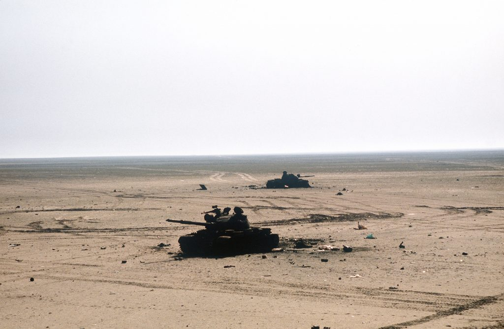 Two destroyed Iraqi T-62 main battle tanks lie in the sand beside a road during the ground phase of Operation Desert Storm. Date: 24 February 1991. Source: DM-ST-91-11595. Author: J.R. Roark, US Marines. Public Domain.