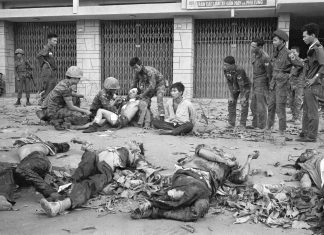 Tet Offensive, Saigon 1968. A Viet Cong prisoner sits next to corpses of 11 of his slain fellow guerrillas after a street fight in Saigon-Cholon on February 11, 1968. In the background are Vietnamese Marines that defeated a Viet Cong platoon holed up in the residential area. The prisoner was later taken out for interrogation. Photo: Eddie Adams/AP. (CC BY 2.0). Source: flickr.com