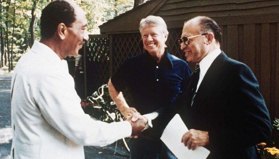 Håndslaget i Camp David: Den zionistiske forbryder Begin med Egyptens præsident Anwar Sadat (de fik Nobels Fredspris i 1978. I baggrunden the fat cat, den amerikanske præsident Jimmy Carter. September 1978. Source: US govt. archives. Photo: ukendt. Public Domain