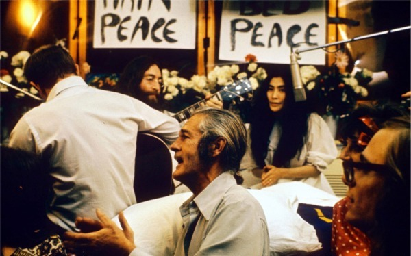 """Recording """"Give Peace a Chance"""". Left to right: Rosemary Leary ( face not visible), Tommy Smothers (with back to camera), John Lennon, Timothy Leary, Yoko Ono, Judy Marcioni and Paul Williams, Date: 1969. Photo: Roy Kerwood – Originally uploaded to English Wikipedia by Roy Kerwood, (CC BY 2.5)."""