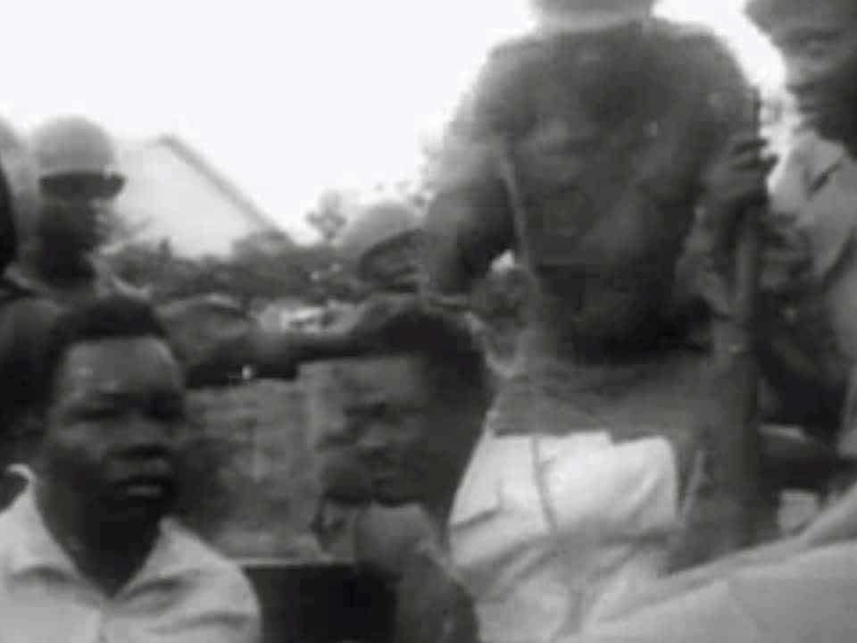 Screenshot of footage of Lumumba (center) under arrest by soldiers before transport to Thysville. The other prisoner is MNC politician Christophe Musungu. 5 December 1960 Source https://archive.org/details/1960-12-05_Lumumba_Seized. Author: Universal Studios.