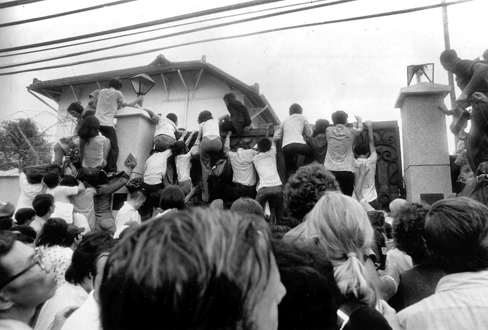 "In this April 29, 1975 file photo, South Vietnamese civilians try to scale the walls of the U.S. embassy in Saigon in an attempt to get aboard evacuation flights. AP Photo/Neal Ulevich. (CC BY-NC 2.0). Source: <a href=""https://www.flickr.com/photos/13476480@N07/40901620445/in/photolist-25jkuLv-2hNJqip-2hBAVYc-2hNRqjs-2hQDgsA-2hNDxyB-2hLZbJG-pSe3sZ-pSe3s8-276TgdW-pSdVtP-pSe3sP-qvSfoG-pRDDDZ-JzAJZU-rxdoHS-25rhnfs-2hNA9U3-pSe3rg-28ch7TT-25rhnfY-2hKRAos-2i2ezxh-2hTNo1F-2i5zEpJ-NAHUT6-2hZX3Cu-28AEAbF-qTigGR-qTG28Z-Uiecjp-qALEAR-pSdVti-qALECV-2i5tkd7-pSe3nZ-2hSwDsw-2hZuvdX-2i3e88v-qALEE8-2hnKgxw-qQLLQt-qyczEC-qQLLRv-2i5F5Mz-2hWXSWL-2hDzLbd-2hBzUpn-2i5yoPW-2i4FPxc"">flickr.com</a>"