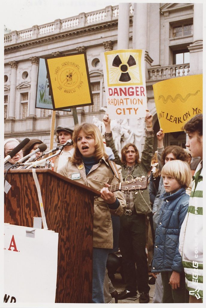 """Singer. Anti-nuke rally in Harrisburg, [Pennsylvania] at the Capitol, 9 April 1979. National Archives at College Park. Photo: unknown. Public Domain. Source: <a href=""""https://commons.wikimedia.org/wiki/File:Singer._Anti-nuke_rally_in_Harrisburg,_(Pennsylvania)_at_the_Capitol._-_NARA_-_540016.tif"""">Wikimedia Commons.</a>"""