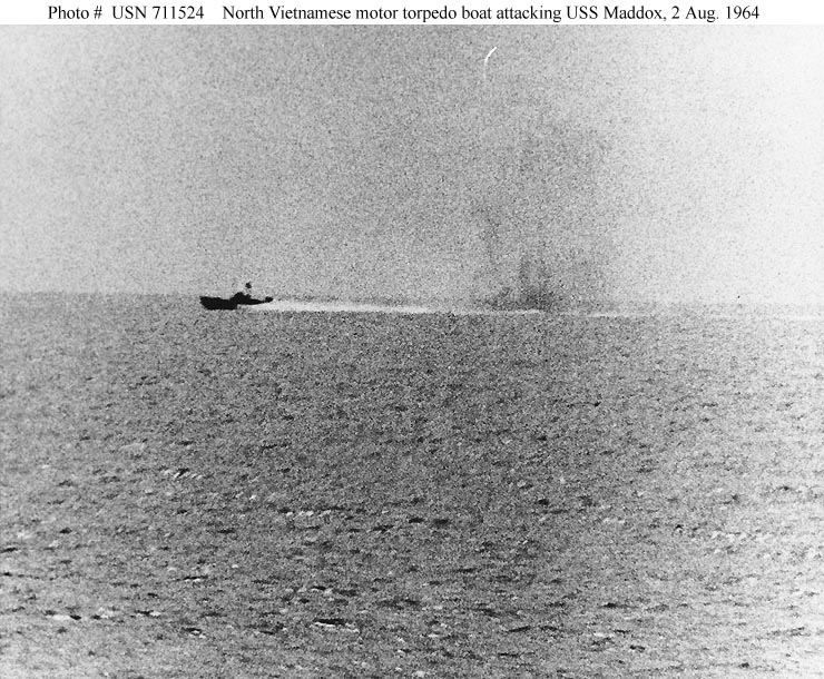Photo #: USN 711524. Tonkin Gulf Incident, August 1964. Photograph taken from USS Maddox (DD-731) during her engagement with three North Vietnamese motor torpedo boats in the Gulf of Tonkin, 2 August 1964. The view shows one of the boats racing by, with what appears to be smoke from Maddox' shells in its wake. Official U.S. Navy Photograph. Public Domain.