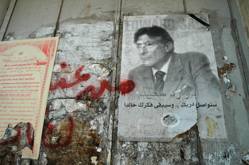 In Memoriam Edward Wadie Said: Ramallah, Graffiti on the West Bank separation wall and a Palestinian National Initiative poster of Professor Edward Said: Scholar, Activist, Palestinian 1935 - 2003 Palestine. Photo: Taken on 24 August 2004 by Justin McIntosh. (CC BY 2.0).