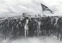 "Raúl Corrales Forno famous image of the victorious 1959 Cuban Revolution entitled ""La Caballería"" (The Cavalry). The image shows a group of Fidel Castro's July 26 Movement rebels mounted on horses and brandishing Cuban flags whipped by the wind. January 1959. Source: Museo de la Revolución, en La Habana, Cuba. Photo: Raúl Corrales Forno. Public Domain."