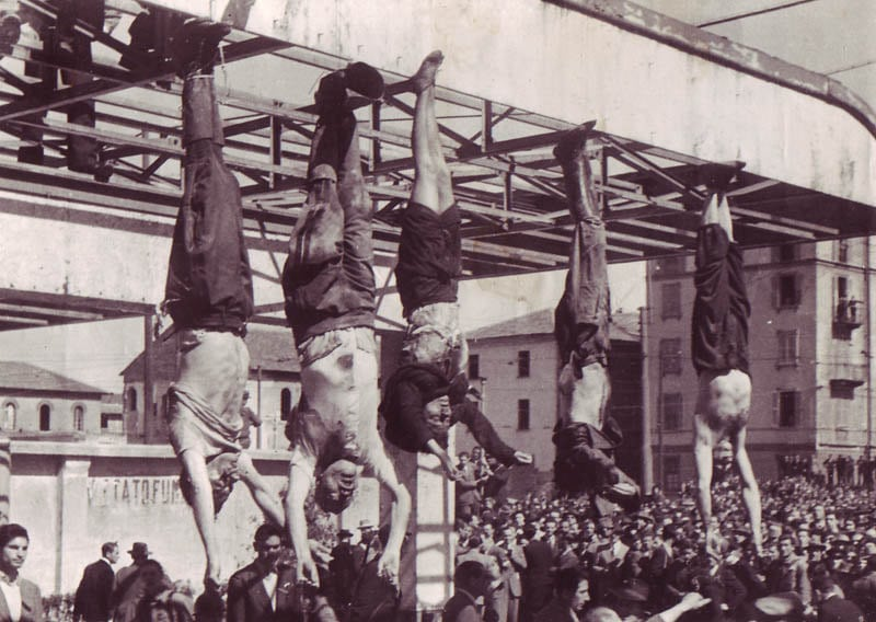 The dead body of Benito Mussolini next to his mistress Claretta Petacci and those of other executed fascists, on display in Milan on 29 April 1945, in Piazzale Loreto, the same place that the fascists had displayed the bodies of fifteen Milanese civilians a year earlier after executing them in retaliation for resistance activity. The bodies, from left to right, are: Nicola Bombacci, Benito Mussolini, Claretta Petacci, Alessandro Pavolini, Achille Starace. The photograph is by Vincenzo Carrese. Public Domain.