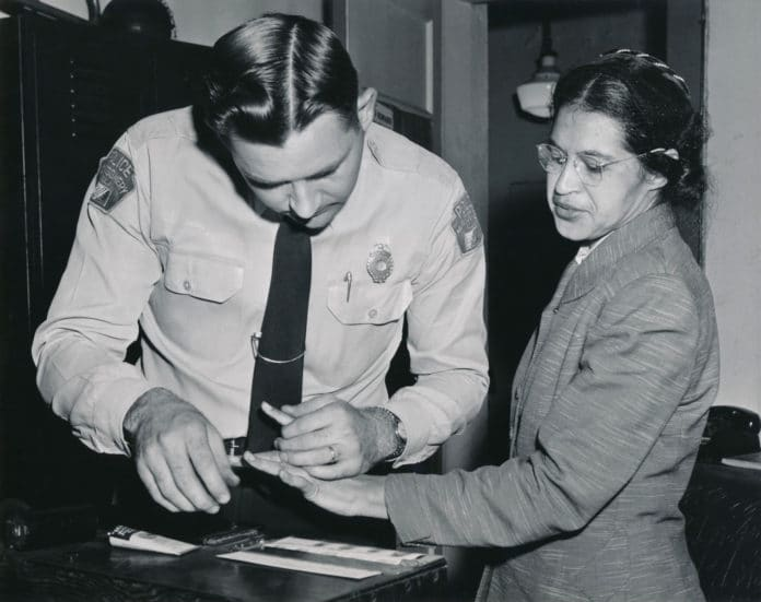 Rosa Parks being fingerprinted in February 22, 1956 by Deputy Sheriff D.H. Lackey following her arrest on December 1, 1955 for refusing to give up her seat for a white passenger on a segregated municipal bus in Montgomery, Alabama. Photo: Associated Press; restored by Adam Cuerden. Public Domain.
