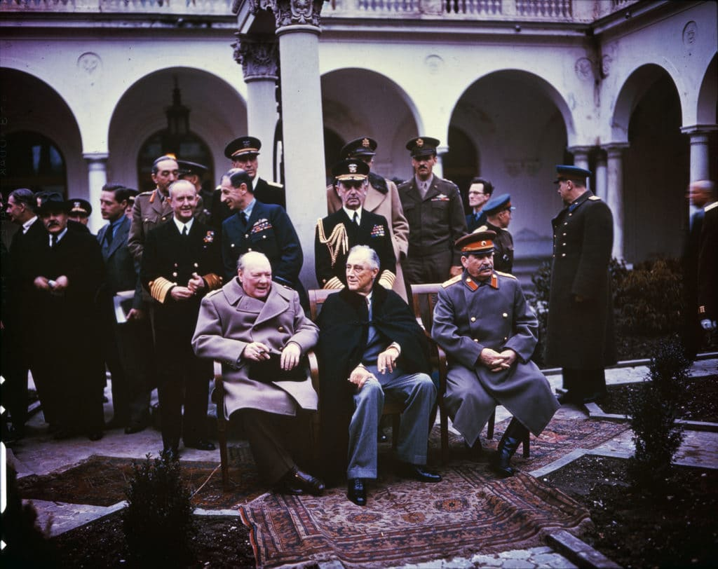 Yalta conference Churchill Stalin Roosevelt 1945 (The National Archives ref: INF 14/447). This Kodak Kodachrome photograph was not colorized. Public Domain.