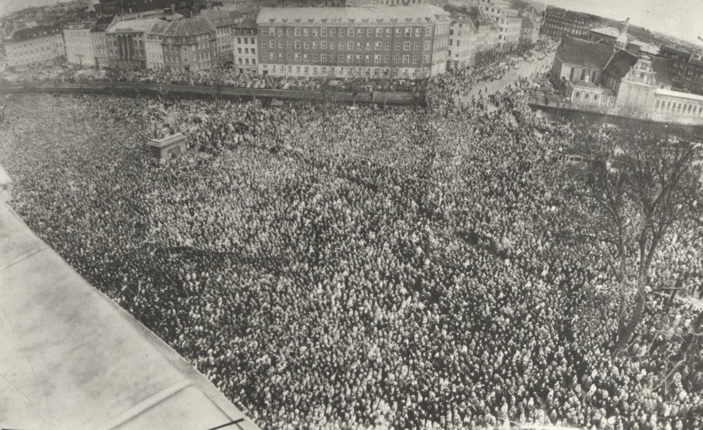 """Demonstrationen den 13. april 1956 foran Christiansborg i protest mod, at Folketinget ophøjede det forkastede mæglingsforslag til lov. Det var her, at Aksel Larsen omtalte de københavnske tillidsmænd som """"situationens generalstab"""", der skulle lede storkonflikten. Den socialdemokratiske statsminister H.C. Hansen skal ved synet af de 200.000 demonstranter have udtalt: """"Mig skal de ikke tage pis på"""" (Arbejdermuseet og ABA)."""