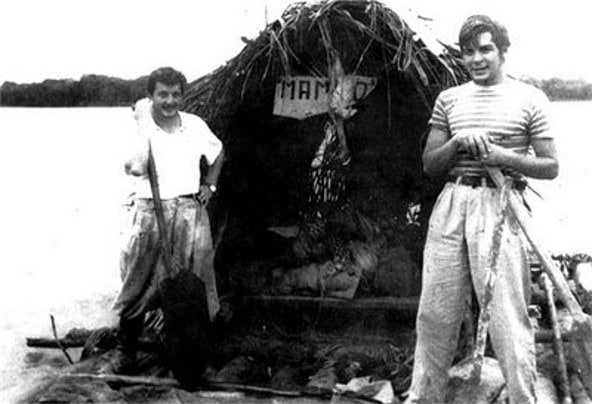 "Ernesto Guevara (right) with Alberto Granado (left) aboard their ""Mambo-Tango"" raft on the Amazon River in June of 1952. Photo: Unknown. Public Domain. Collection: Museo Che Guevara (Centro de Estudios Che Guevara en La Habana, Cuba)."