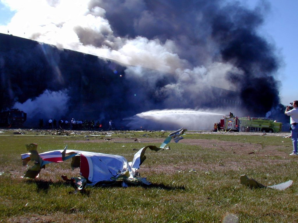 Wreckage from the hijacked American Airlines FLT 77 sits on the west lawn of the Pentagon minutes after terrorists crashed the aircraft into southwest corner of the building. The Boeing 757 was bound for Los Angeles with 58 passengers and 6 crew. All aboard the aircraft were killed, along with 125 people in the Pentagon. U.S. Navy Photo by Journalist 1st Class Mark D. Faram. Date: 11 September 2001. Source: 010911-N-6157F-001 from http://www.navy.mil/view_image.asp?id=2445 . Author: U.S. Navy Photo by Journalist 1st Class Mark D. Faram. (RELEASED) Public Domain.