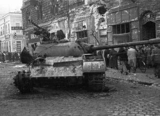 Hungary, Budapest IX, 1956 Damaged Buildings and a wreck of a Soviet tank at the corner of Berzenczey Street, Tatras (later Balaton) cinema. Photo:FORTEPAN / Nagy Gyula. (CC BY-SA 3.0).