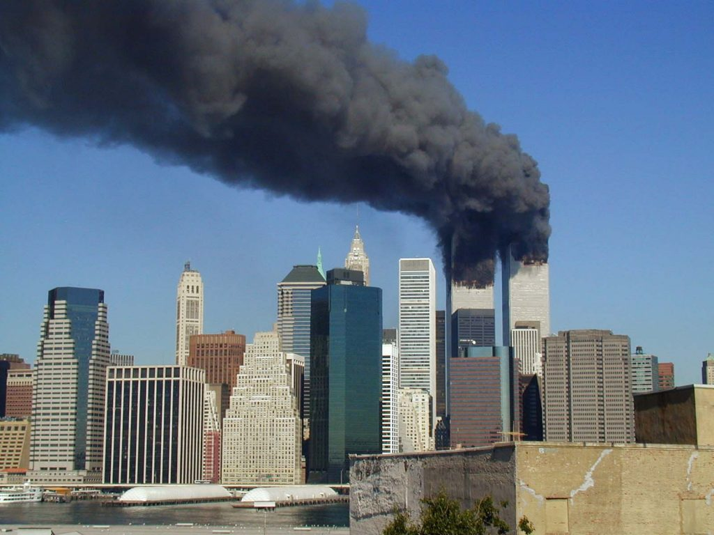 Plumes of smoke billow from the World Trade Center towers in Lower Manhattan, New York City, after a Boeing 767 hits each tower during the September 11 attacks, as seen from the Brooklyn Promenade. Source: Flickr. Author: Flickr user Michael Foran. (CC BY-NC-SA 2.0)