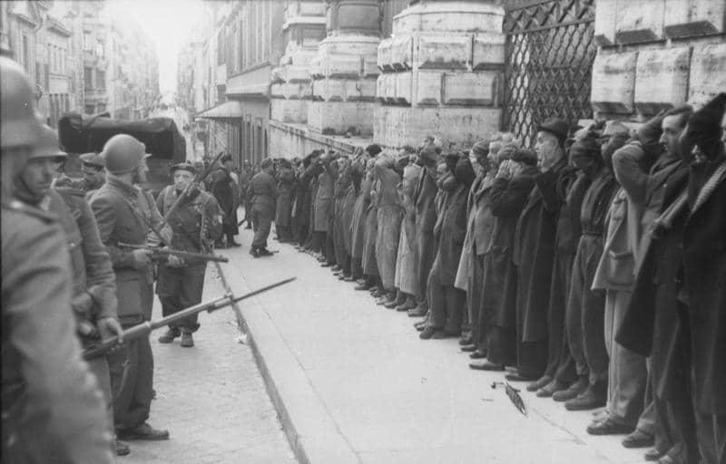 """Tyske og italienske soldater indfanger civile gidsler, der myrdes 24.3.1944 i Ardeatiner-grotterne. Foto: Bundes Archiv. Kilde: <a href=""""https://commons.wikimedia.org/wiki/File:Bundesarchiv_Bild_101I-312-0983-03,_Rom,_Festnahme_von_Zivilisten.jpg"""">Wikimedia Commons</a>"""