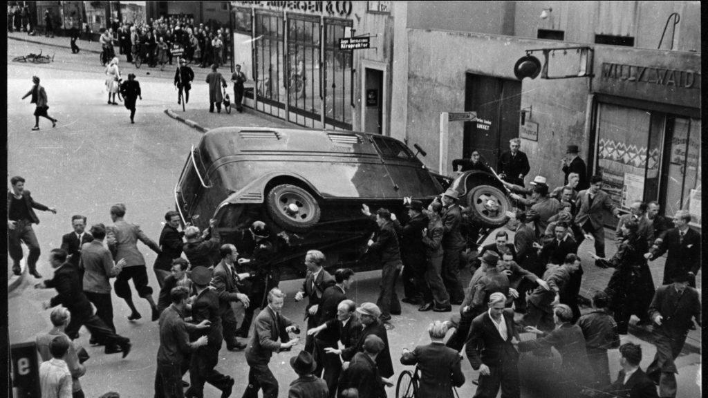 En politibil væltes under optøjer i Odense, august 1943. Fotograf: Ukendt/Nationalmuseet. (CC BY 2.0).
