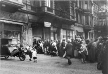 Distress of the 1920s. People stand in line in front of a shop. Photo: Unknown/German Federal Archives. (CC BY-SA 3.0 DE).