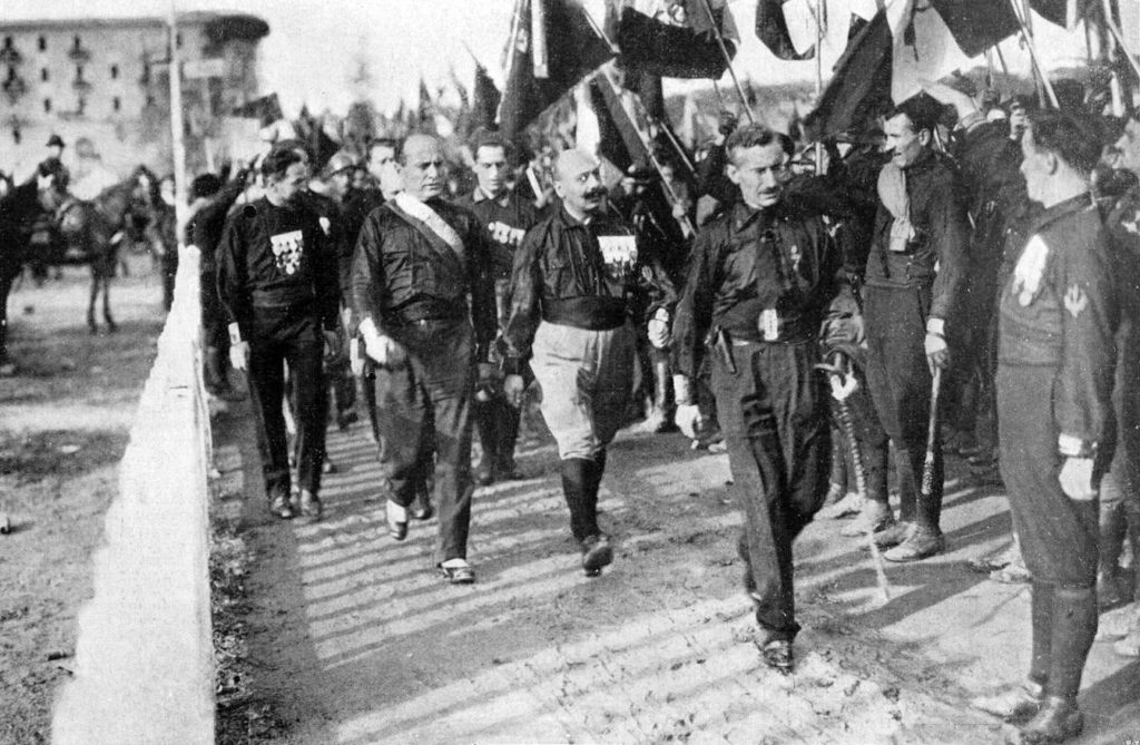 Fascist march on Rome. From left to right: Italo Balbo, Benito Mussolini, Cesare Maria de Vecchi and Michele Bianchi, 24. oktober 1922. Photo: Unknown / Illustrazione Italiana, 1922, n. 45. Public Domain.