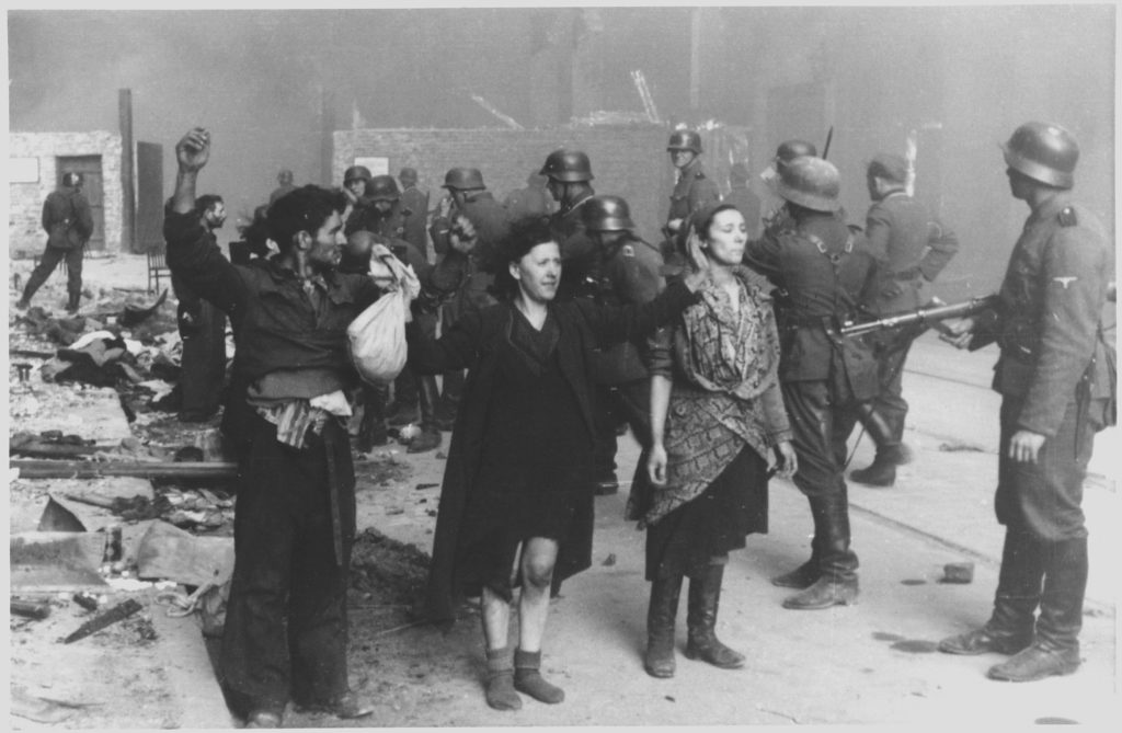 Jews captured by Waffen SS soldiers during the suppression of the Warsaw Ghetto Uprising. Photograph from a report filed by Juergen Stroop, commander of the German forces that liquidated the ghetto. Poland, April-May 1943. To the right Hasia Szylgold-Szpiro. Photo: Unknown/SS. Public domain.