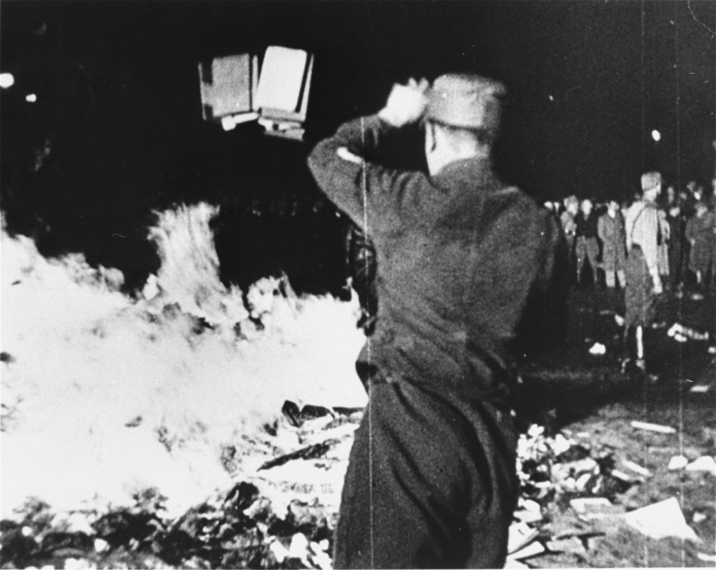 """A member of the SA throws confiscated books into the bonfire during the public burning of """"un-German"""" books on the Opernplatz in Berlin. 10 May 1933. Photo: Unknown. Public Domain."""