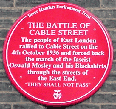 Red plaque commemorating The Battle of Cable Street. Location: Dock Street, near Cable Street junction, London, 17 Sept 2005. Photographer: Richard Allen. Public Domain.