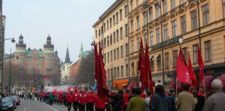"""1. maj demonstration med røde faner, Stockholm, Sverige 2006. Foto: ukendt, Public Domain. - """"Når jeg ser et rødt flag smælde"""" er skrevet af Oscar Hansen. Se nedenfor 23 juli 1895."""