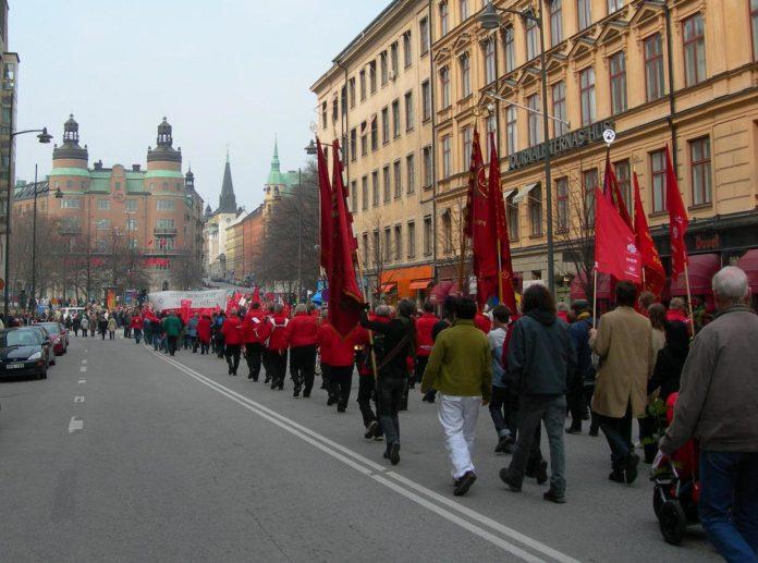 1. maj demonstration med røde faner, Stockholm, Sverige 2006. Foto: ukendt, Public Domain. -