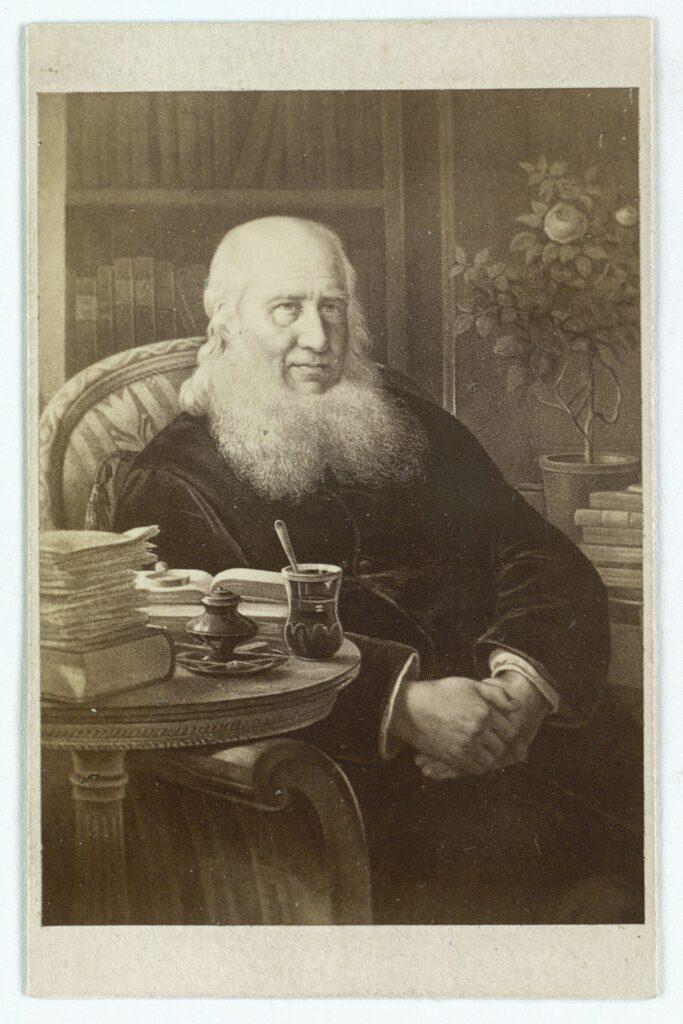 Portrættet viser den næsten 80-årige N.F.S.Grundtvig i fuld vigør, med opslåede bøger på bordet. Visitkort foto efter maleri fra 1862 af Wilhelm Marstrand (1810–1873). (CC BY-NC-ND 4.0).