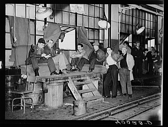 """Strikers guarding window entrance to Fisher body plant number three. Flint, Michigan. 1937 Jan.-Feb. Source: Farm Security Administration - Office of War Information Photograph Collection (Library of Congress LC-USF34-040028-D). Photo: Sheldon Dick. Public Domain. Source: <a href=""""https://commons.wikimedia.org/wiki/File:Flint_Sit-Down_Strike_window.jpg"""">Wikimedia Commons</a>."""