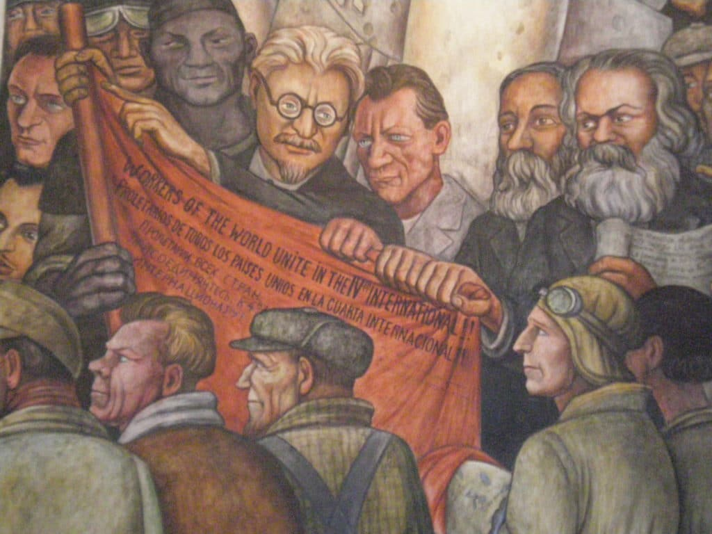 Detail from Diego Rivera's fresco 'Man at the Crossroads' at the Palace of Fine Arts, Mexico City. There are notably represented Leon Trotsky, holding the red flag of the Fourth International, Friedrich Engels and Karl Marx (pass the cursor of the mouse on the image to identify them). Date of photo: August 28, 2009. Author Painting: Diego Rivera; photo: Lock. (CC BY 3.0).