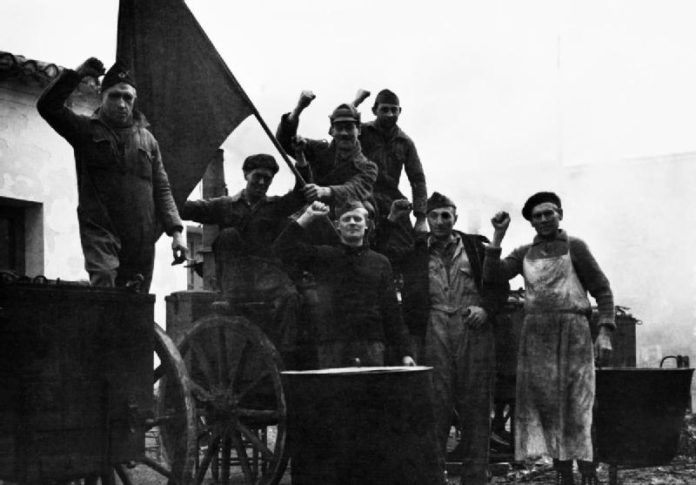 The International Brigade during the Spanish Civil War, December 1936 - January 1937. Members of the International Brigade in the British cookhouse at Albacete raise their fists in the Communist salute. Photo: Vera Elkan. Public Domain.