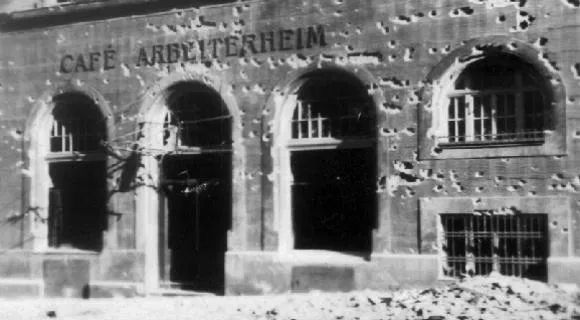 "Wien 1934, facade with bullet holes and the inscription ""Café Arbeiterheim""."