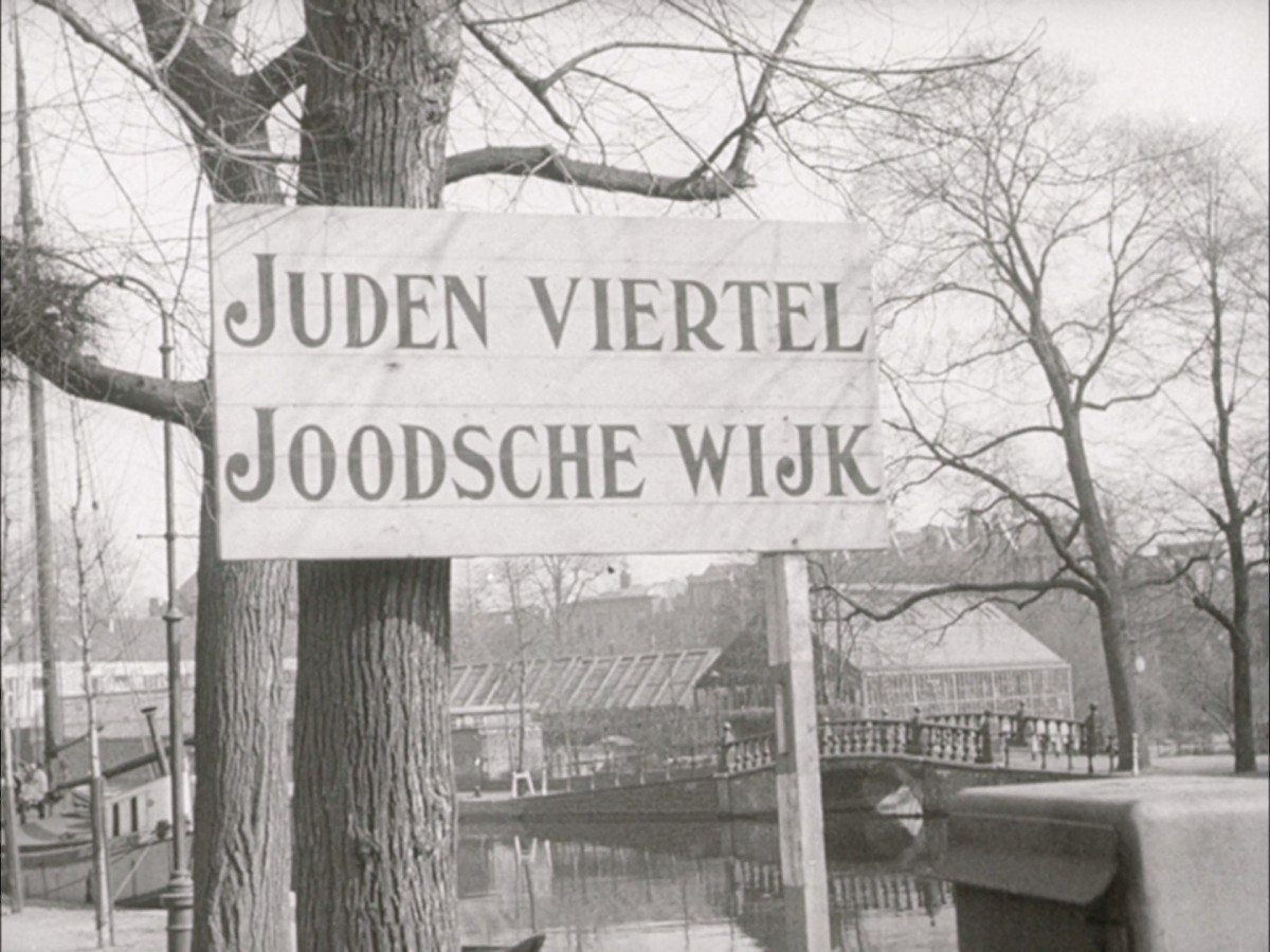 Jewish Ghetto in Amsterdam, Nederlands. WS street with large street sign: JUDEN VIERTEL JOODSCHE WIJK. 1942. See about the Dutch protests against persecutions of jews, January 25. 1941. Accessed at US Holocaust Memorial Museum, courtesy of Nederlands Instituut voor Beeld en Geluid.