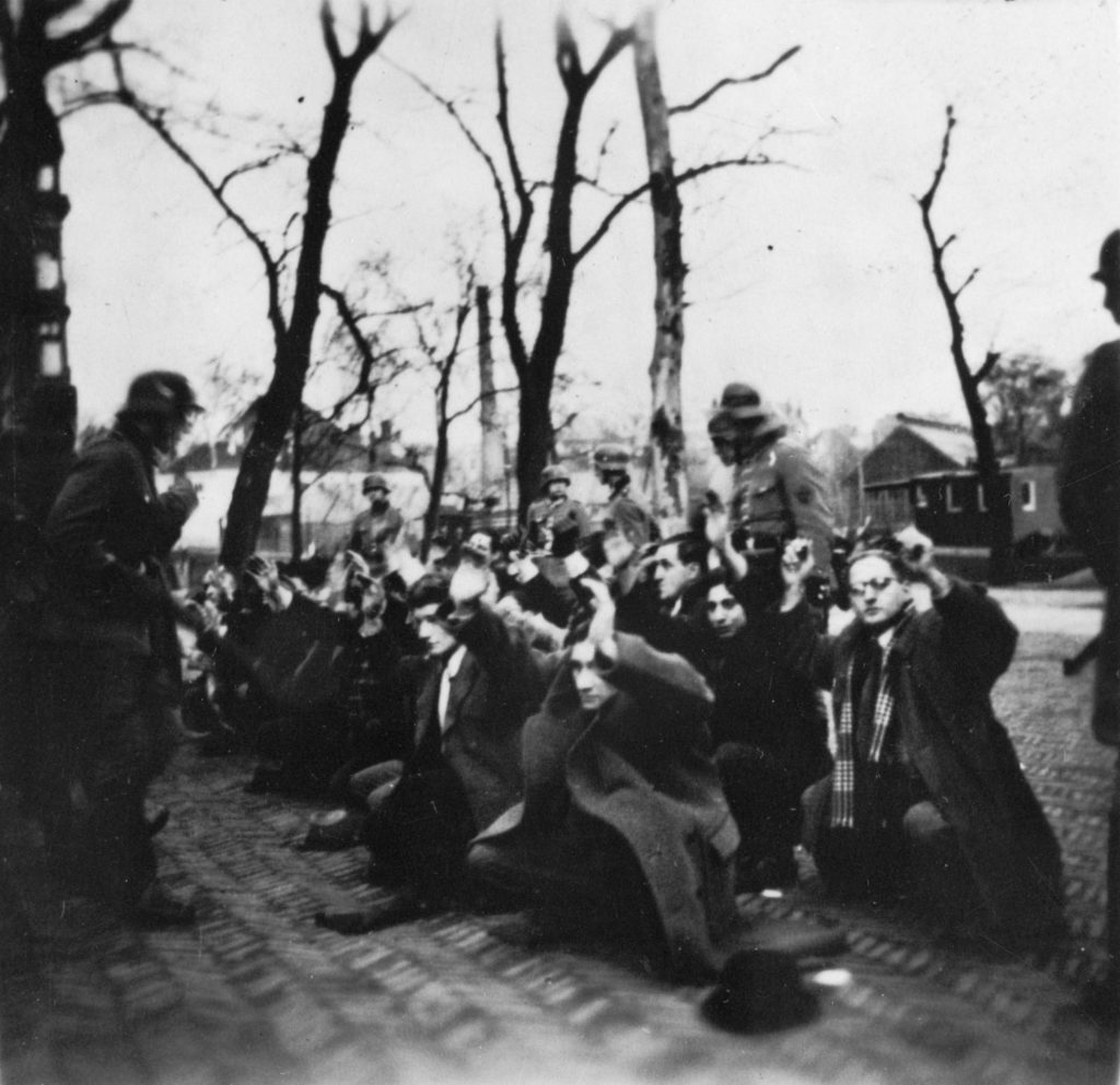 German raid on Jonas Daniël Meijerplein in Amsterdam / Photo of a group of men on their knees, guarded by German soldiers. 25-26 Feb 1941 or 1 May 1940. Photo collection Government Information Service, Photographer unknown/Source National Archive. Public Domain.
