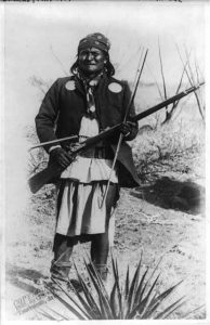 Scene in Geronimo's camp...before surrender to General Crook, March 27, 1886: Geronimo, full-length portrait standing, facing left, rifle at port, circa 27 March 1886. Photo: C. S. Fly (1849–1901). Public Domain.