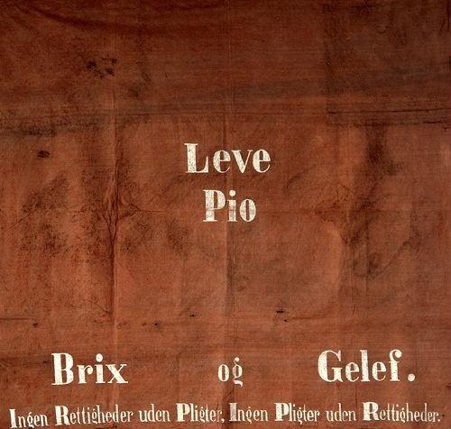 Banner, som hylder Den Internationale Arbejderforenings ledere Louis Pio, Harald Brix og Paul Geleff. Banneret blev beslaglagt af politiet i forbindelse med forbudet mod Internationalen i 1873 og først leveret tilbage i 1931. Tilhører Arbejderbevægelsens Bibliotek og Arkiv.