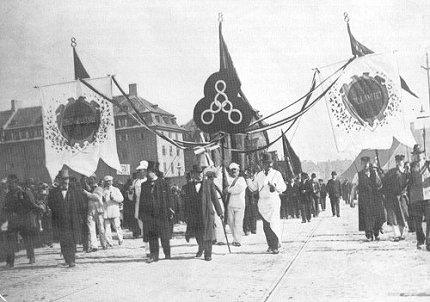 1. maj demonstration i 1900. Efter beslutninger på en international kongres i 1889 om at fejre 1. maj som international kamp- og festdag måtte de danske arbejdere under trussel om afskedigelse i de første år holde demonstrationen på den nærmeste søndag. Men fra slutningen af 1890'erne accepterede arbejdskøberne, at arbejderne kunne få fri på selve dagen. De 3 otte-taller symboliserer kampen for 8 timer arbejde, fritid og hvile. ABA.