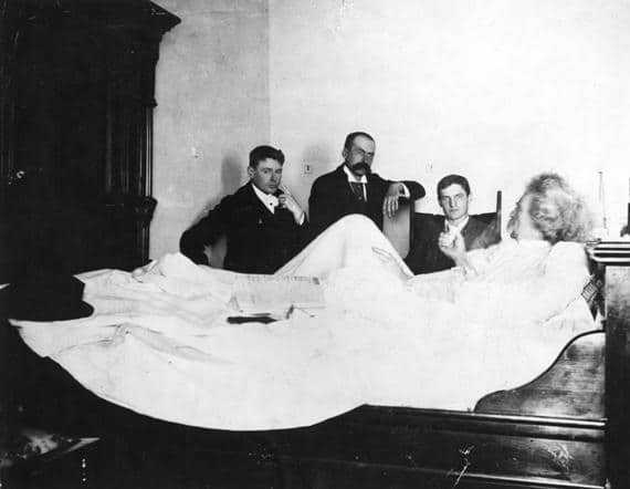 Mark Twain being interviewed by Ernest John Harrison and other reporters from his hotel bed in Vancouver on August 18, 1895. Photo: George Thomas Wadds (1874–1962), photographer. Public domain.