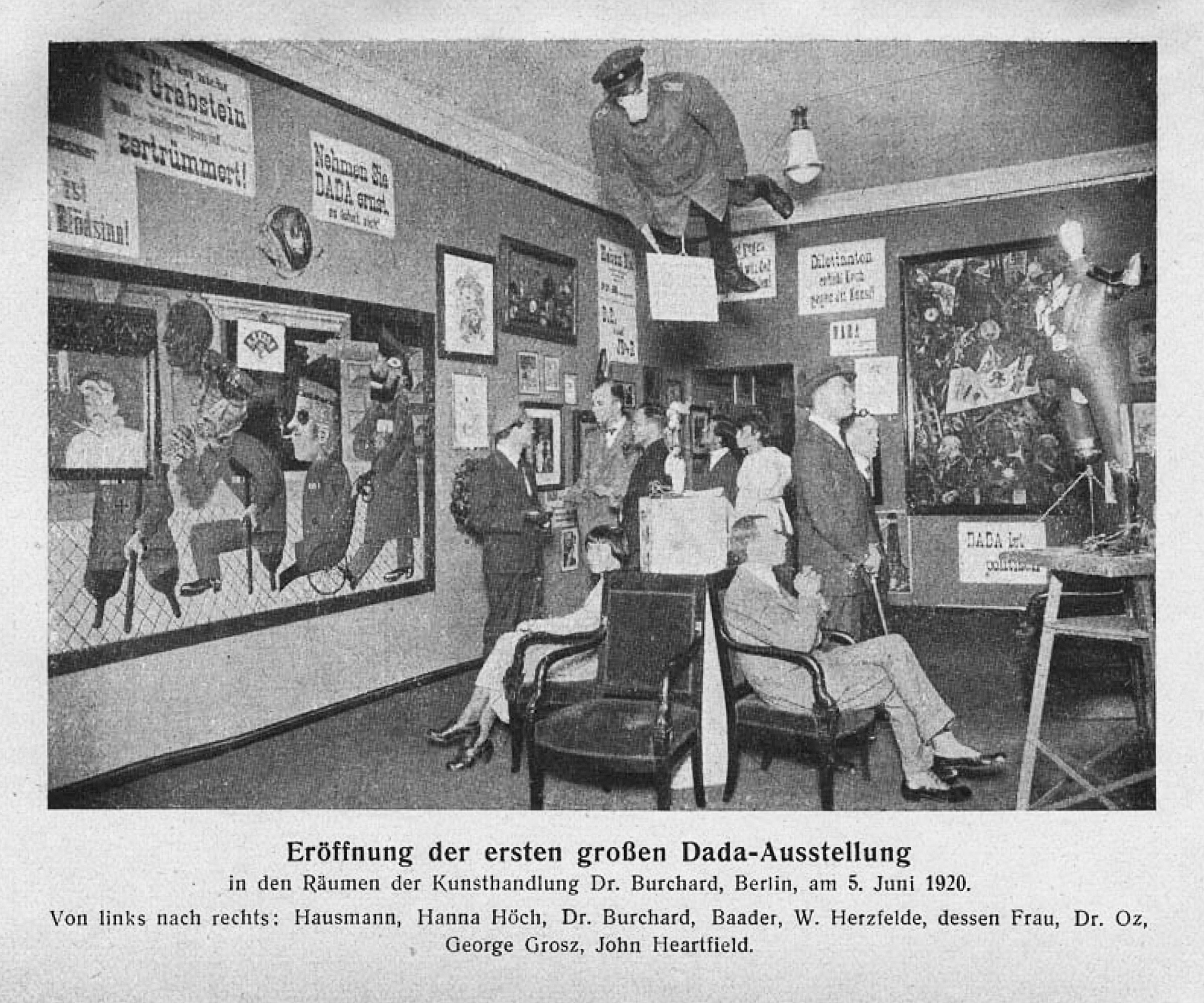 Grand opening of the first Dada exhibition, Berlin, 5 June 1920. The central figure hanging from the ceiling was an effigy of a German officer with a pigs head. From left to right: Raoul Hausmann, Hannah Höch (sitting), Otto Burchard, Johannes Baader, Wieland Herzfelde, Margarete Herzfelde, dr. Oz (Otto Schmalhausen), George Grosz and John Heartfield. Photo: Unknown. Public Domain.