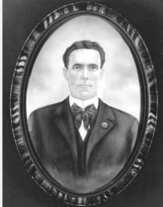 """Joe Hill. Photograph of a painting of unknown oainter between 1906 and 1915. Handwritten on verso of image: Joe Hill, IWW organizer, poet, martyr. Location: University oif Washington. Public Domain. Source: <a href=""""https://commons.wikimedia.org/wiki/File:Joe_Hill_(PORTRAITS_46).jpg"""">Wikimedia Commons</a>."""