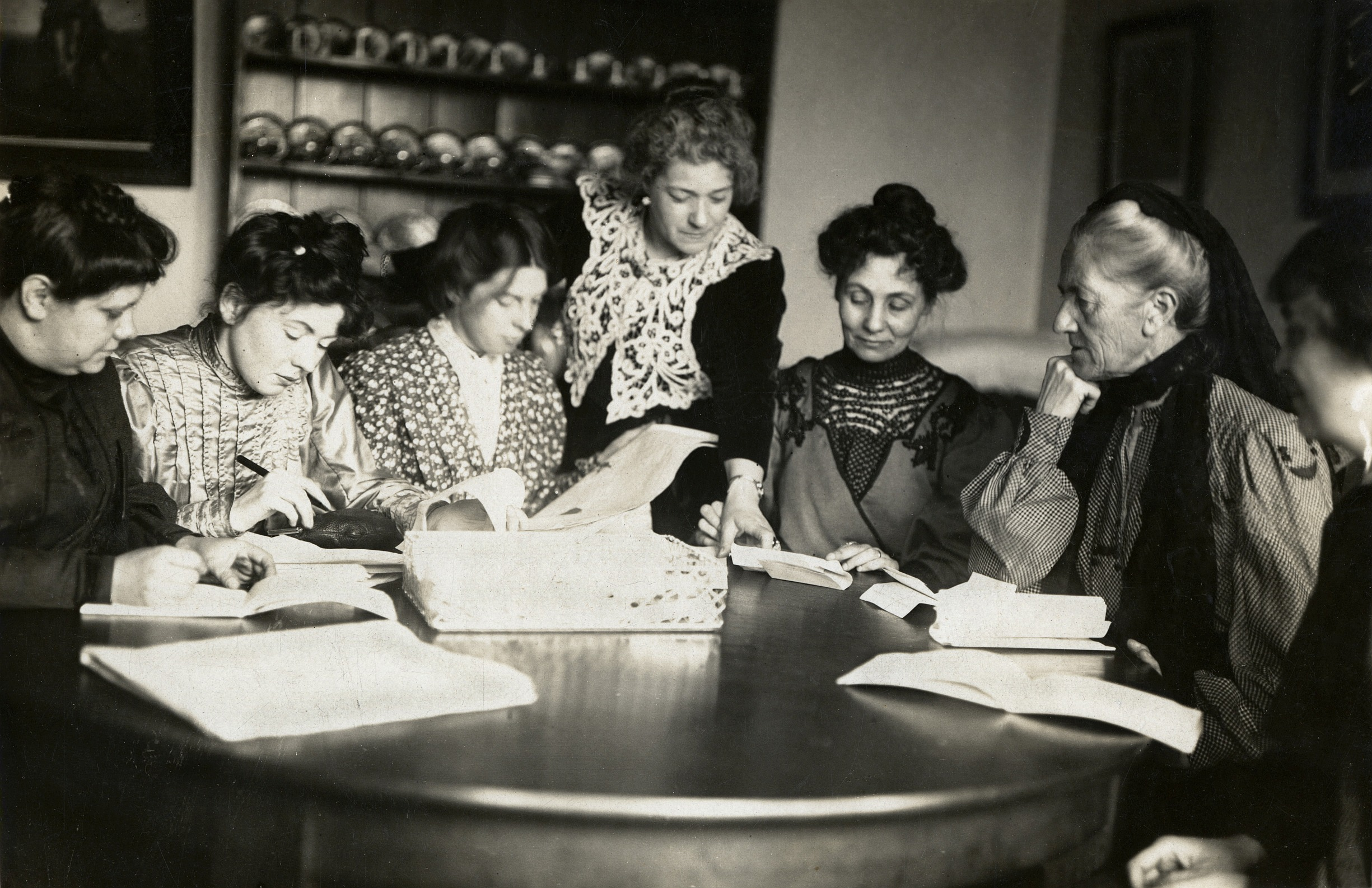 Meeting of Women's Social and Political Union, Flora Drummond, Christabel Pankhurst, Annie Kenney, Emmeline Pankhurst, Charlotte Despard with two others, working round a kitchen table; printed inscription on reverse 'Barratt's Photo Press Agency, 8 Salisbury Ct, Fleet St, EC'. Photo: The Women's Library collection/Library of the London School of Economics and Political Science. No known copyright restrictions.