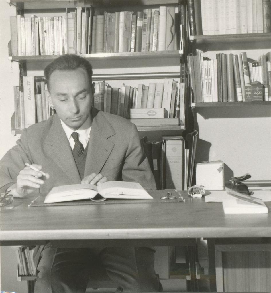 Primo Levi sitting at the desk while reading with a cigarette in his hand - shelves with books in the background, circa 1960. Photo: Anonymous. Public Domain.